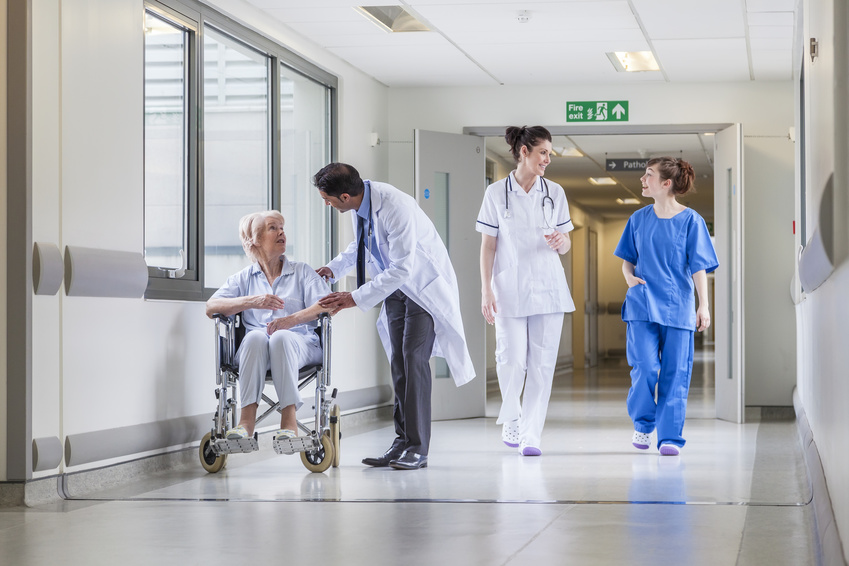 Senior female woman patient in wheelchair sitting in hospital corridor with Asian Indian male doctor and female nurse colleagues