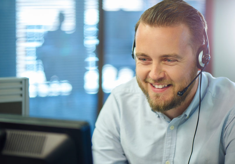 a bearded call centre representative is happily chatting on a headset to a customer . He is sitting in an open plan call centre , with a manager's office in the background with an unrecognisable meeting taking place .